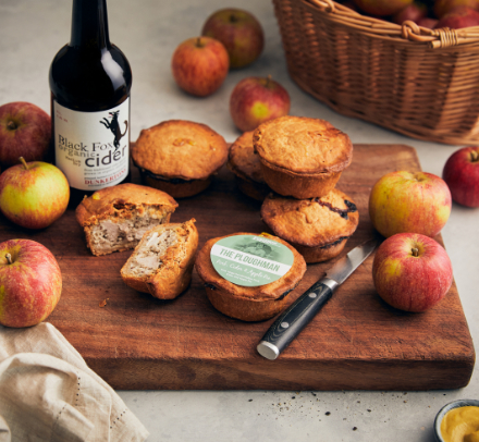 Pork pies, apples and cider on a chopping board